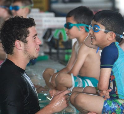 Swim instructor talking to students