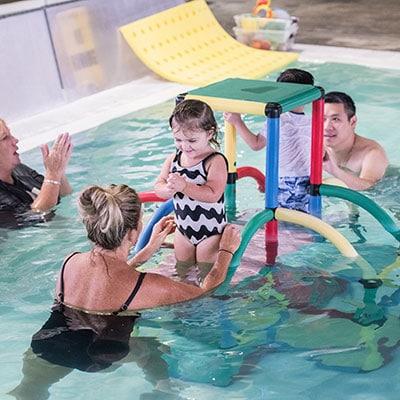 Parents with their children in swim school