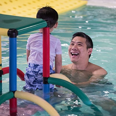 Father smiling at son in the pool