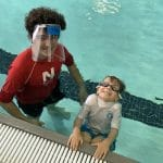 swim coach wearing mask teaching swimming