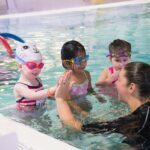 swim instructor giving a student a high five